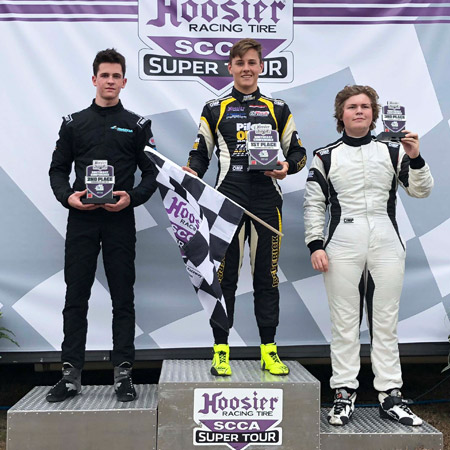 pilot one racing | kaylen frederick | winners podium with kaylen in 1st holding trophy and checkered flag